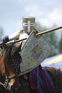 Image:  Medieval knight in full armor on horseback at a jousting competition.